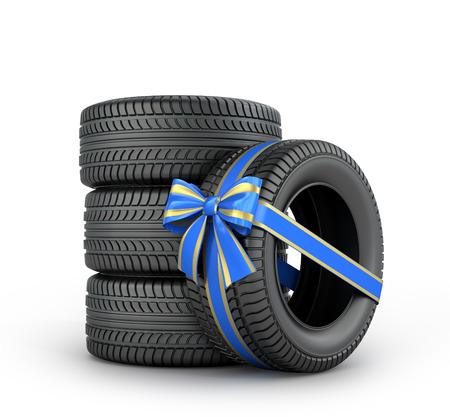enveloped: Car tires enveloped ribbon with a bow on a white background.