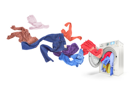 Colored laundry flying from washing machine, isolated on white background Stock Photo