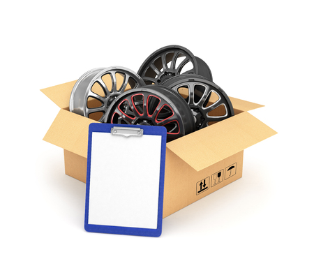 rims: Automobile rims in an open cardboard box with a folder for documents
