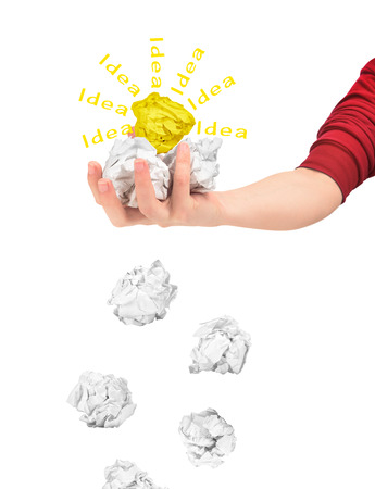imagine a science: The concept of weeding out the ideas. Hand holding crumpled paper balls isolated on white background. Stock Photo