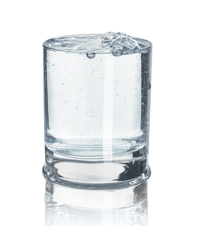 reflection: an overly full glass of water with reflection on an isolated white background