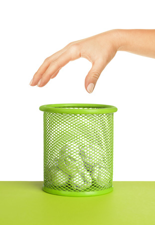 wastebasket: hand near wastebasket full of waste paper and fly ball Stock Photo