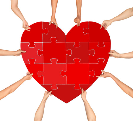 many hands: many hands holding puzzle heart isolated on a white background Stock Photo