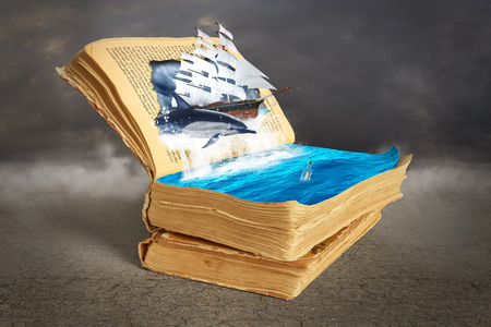 book concept: Concept of reading. Opened magic book with torn page.Dolphin and sailing ship jumps out of the page into water, bottle with a message. Concept of dreaming. Stock Photo