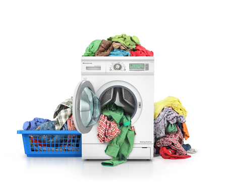 Concept of a big washing. Clothes falling from the washing machine with pile of clothing near it. Clothes in the basket.