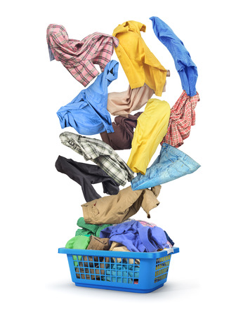 Colorful clothes fall in a full laundry basket isolated on white background. Reklamní fotografie