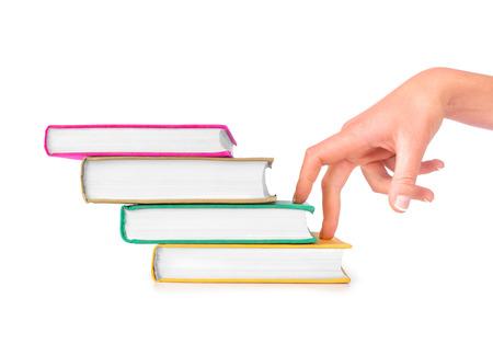 hardback: Fingers moving up hardback book steps concept for learning, improvement and progress through education