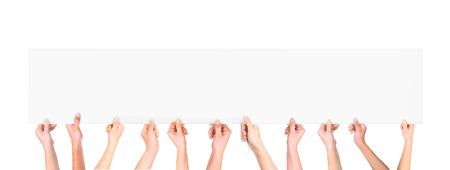 Many hands holding a blank poster for advertising on an isolated white background Stock Photo