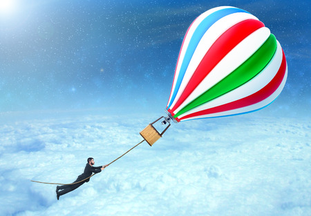 surrealistic: Concept of freedom. A man being lifted by aerostat. Concept of travel. Flying of fantasy