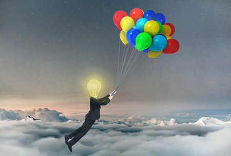 lifted: Concept of freedom. A businessman being lifted by balloons with glowing light bulb a head. Concept of idea.