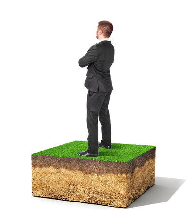 stubbornness: The concept of property. A man is standing on a piece of land isolated on a white background.