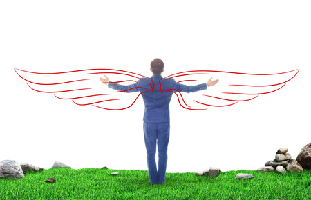 Concept of achievement of success. Standing man on grass over the precipice with raised arms and imaginary wings on white background. Concept of power.