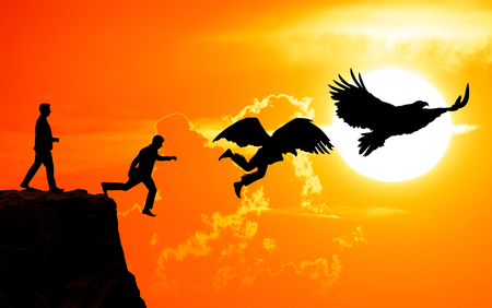transforms: The concept of freedom. A man jumps from a rock and transforms into a bird against the background of a sunset. The concept of success.