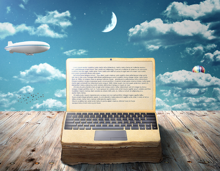 The concept of e-book. An open book as laptop lies on a wooden table against the sky. Writing. 스톡 콘텐츠
