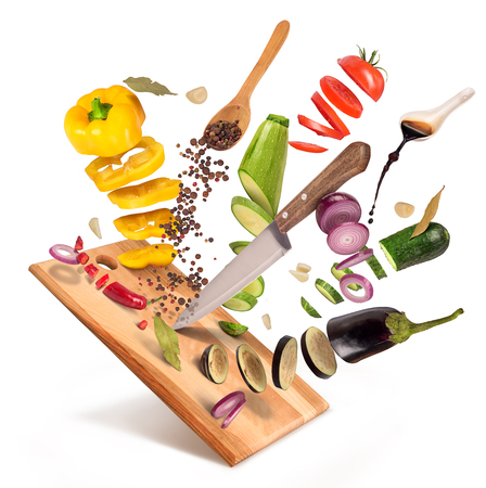 Flying slices of sliced vegetables are served on a wooden board on a white background.
