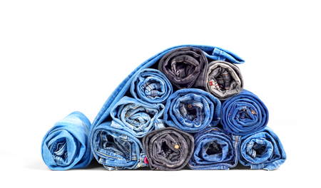 Stack of twisted jeans isolated on a white background Stock Photo