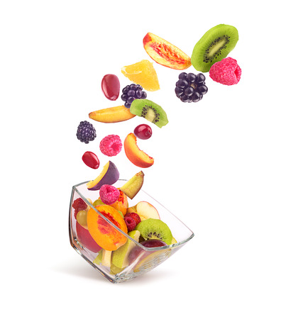 fruit salad ingredients in the air in a glass bowl isolated on white background Standard-Bild