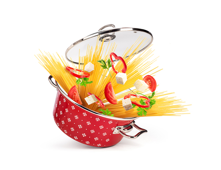 Red saucepan with pasta and cheese with vegetables, isolated on white background Stock Photo