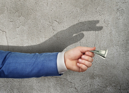 The concept of manipulation. The hand giving money casts a shadow in the form of a puppeteers hand.