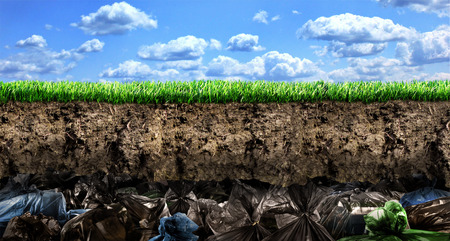 Ð¡oncept of global pollution. A large pile of garbage in the section of the earth against the background of nature.