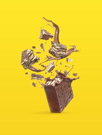 Waffeln werden in Stücke zerbrochen, wobei ein Schokoladenspritzer auf einem hellen Hintergrund isoliert wird