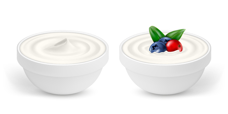 Ceramic bowls of white yogurt with berries isolated on white background