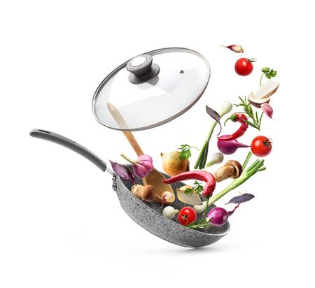 Composizione vegetale. Padella con coperchio e verdure volanti, isolato su sfondo bianco Archivio Fotografico