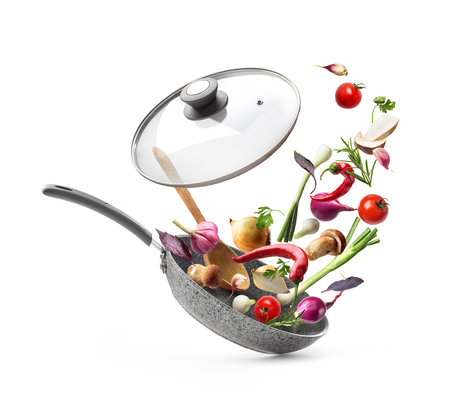 Gemüsezusammensetzung. Bratpfanne mit Deckel und fliegendem Gemüse, lokalisiert auf weißem Hintergrund Standard-Bild