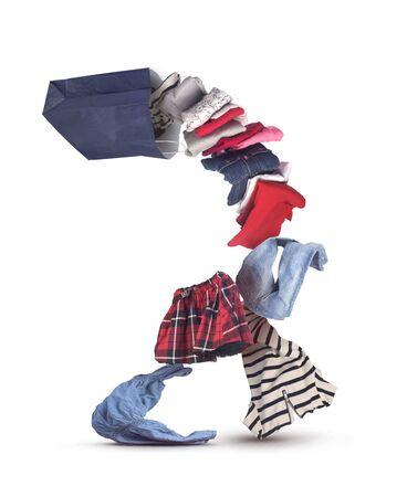 pila di vestiti che cadono fuori dalla borsa della spesa isolato su bianco
