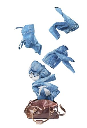Jeans clothes flying from broun skin luggage bag isolated on a white background