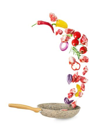 Cooking concept. Vegetables and meat are falling on a pan isolated on white background. Healthy food. Stok Fotoğraf
