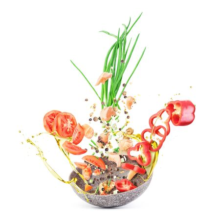 Cooking concept. Vegetables and meat are falling on a pan isolated on white background. Healthy food. Zdjęcie Seryjne