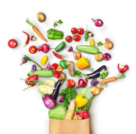 La comida sana se vierte de una bolsa de papel sobre un fondo blanco.