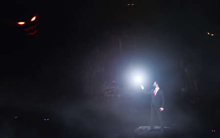 Phobia research concept. A man in a dark cave with light against monsters.