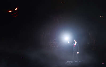 Fear therapy concept. A man in a dark cave with light against monsters. Foto de archivo