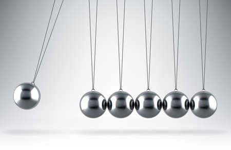 Balancing balls Newton's cradle hanging on gray background