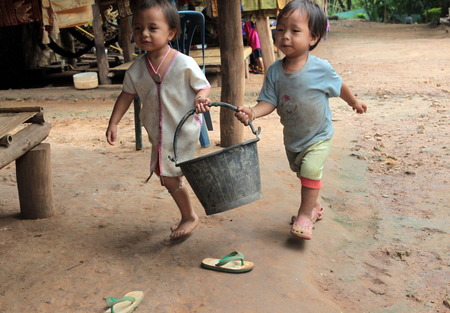 Two children fetch water at the village fishing north of Chiang Mai in northern Thailand