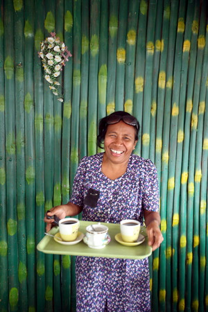 A woman while serving coffee at a restaurant in Manatuto on the north coast of East Timor on the island of Timor separated into two in Asia