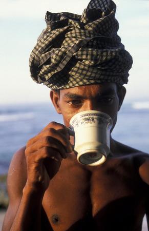 asien: Asien, Indischer Ozean, Sri Lanka, Ein Tee trinkender Traditionelle Fischer sogenannte Stelzenfischer beim Fischen in der naehe des Kuestendorf Ahangama an der Suedkueste von Sri Lanka. (URS FLUEELER)