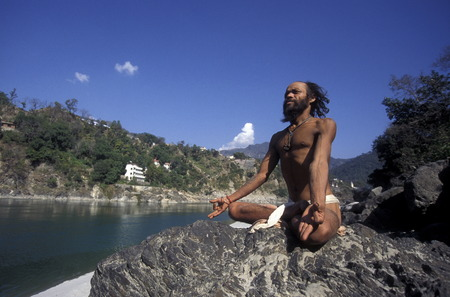 uttar pradesh: a men on the Ganges River in the town of Rishikesh in the Province Uttar Pradesh in India.