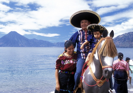 People at the coast of Lake Atitlan mit the Volcanos of Toliman and San Pedro in the back at the Town of Panajachel in Guatemala in central America. Editorial