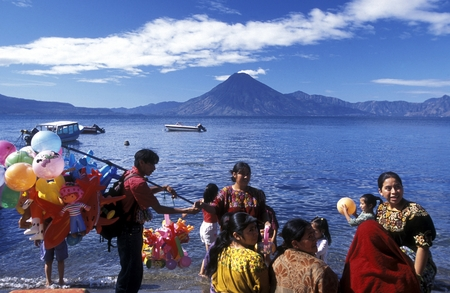 landschaft: People at the coast of Lake Atitlan mit the Volcanos of Toliman and San Pedro in the back at the Town of Panajachel in Guatemala in central America.