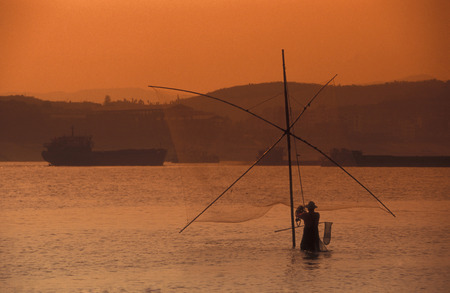 three gorges: a fishing boatin yangzee the river in the city of Yichang near the three gorges dam project in the province of hubei in china.