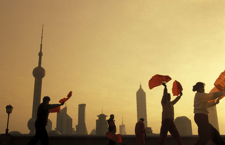 people celebrathing tai chi in the morning on the Bund in front of the skyline of Pudong in the City of Shanghai in China.