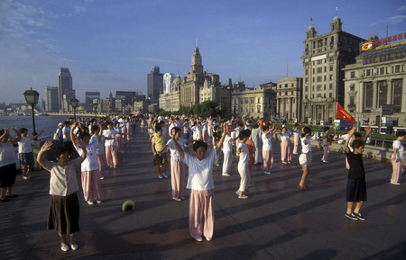 people dancing in the morning on the Bund in front of the skyline of Pudong in the City of Shanghai in China.