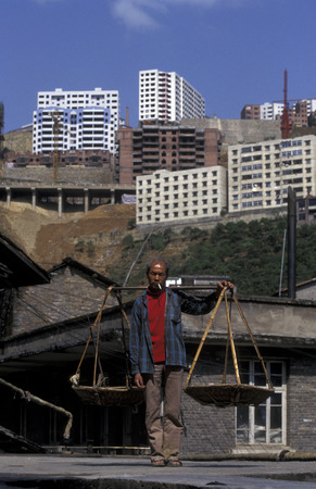 three gorges dam: a men in the old city with the new city in the back in the city of wushan on the yangzee river near the three gorges valley up of the three gorges dam project in the province of hubei in china.