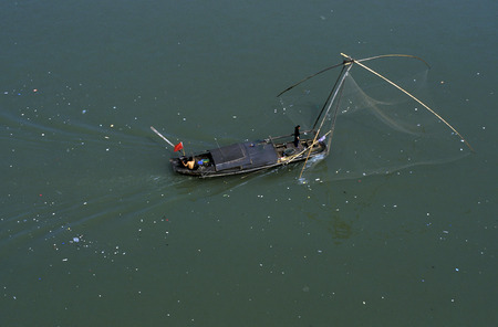 three gorges dam: a fishing boatin yangzee the river in the city of Yichang near the three gorges dam project in the province of hubei in china.