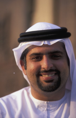 souq: a portrait of a Arab men in the souq or Market in the old town in the city of Dubai in the Arab Emirates in the Gulf of Arabia.