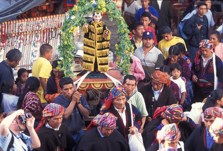 indios: A relogion  procession with people in traditional clotes at the Market in the Village of  Chichi or Chichicastenango in Guatemala in central America.