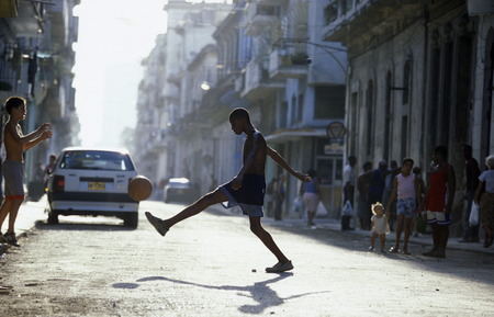 people play soccer in the old town of the city Havana on Cuba in the caribbean sea.